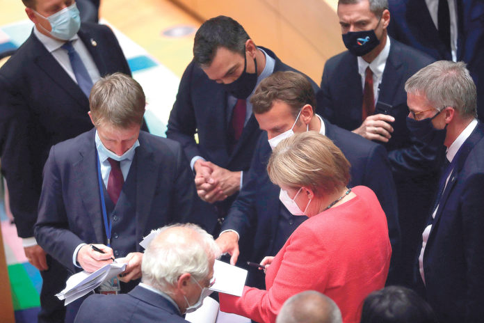 La canciller alemana Angela Merkel conversa con el presidente francés Emmanuel Macron, el presidente español Pedro Sánchez y otros dignatarios. EFE